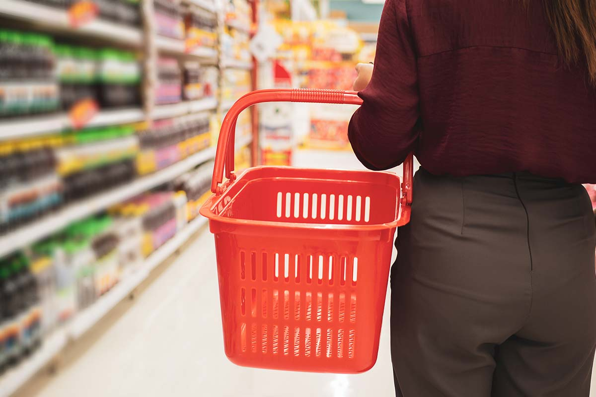Woman with basket in supermarket